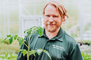 Ben Casteel holding a plant in the Greenhouse